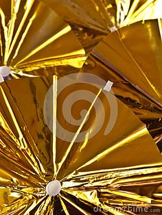 A closeup of gold shiny plastic cocktail parasols