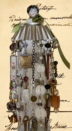 Karen Burns. Karen used all the client's mother's momentos in this piece. Tart pan is attached to the lid of the bottle where the client can add more momentos.