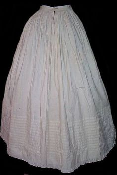 C.1860 -1862. It was considered a faux pas for the ridges of your hoops to show through your skirt. to fix this, women wore full petticoats, as wide as their outer skirts, to go over the crinoline, to soften the edges of the hoops so they wouldn't show through. They would also add volume to a skirt making it bigger as well.   This petticoat is made of cotton, and is decorated with little pintucks and crimped fabric around the hem. It looks like it was made for a young girl of around 10.