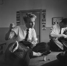 DigitaltMuseum - Två unga män sitter och syr på ett bord med benen i kors i…