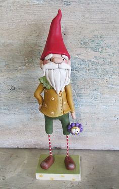DESCRIPTION: Garden Gnome with tall red gnome cap and flower charm in hand. This is a taller gnome that measures 8.5 inches in height. Hes got a tall crooked top red cap, textured beard, texture swirl collar, a daisy painted mustard yellow jacket, striped legs and in one hand a purple flower character charm. Base is hand cut wood from a local woodworker. ARTIST: I am a long time artist of over 17 years in the same medium of clay art. My background includes thousands of these characters all…