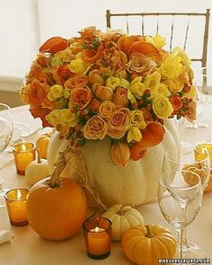 fall wedding centerpiece ideas: put orange and yellow color flowers in big pumpkin and use small pumpkin side for deco