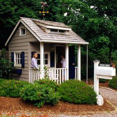 A few shrubs soften the landscape outside this traditionally styled playhouse. The simpler the materials and finishes, the easier the upkeep; here, a layer of mulch around the bushes and building eliminates the need for mowing./