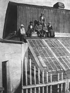The former tsar Nicholas II and his children sitting on the roof of a greenhouse during their captivity in Tobolsk.