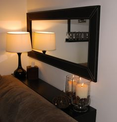 Horizontal mirror above couch with DIY shelf behind sofa.