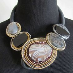 This grey collar style necklace is comprised of genuine grey agate and black onyx stones accented with Japanese gold and silver seed beads. A hidden closure on the front of the necklace behind the gemstones makes this piece both unique and striking.