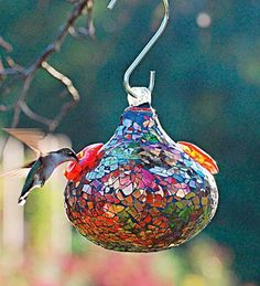 "heavy plain glass ""bulb""..lightly mosaic'd..with old or new broken christmas bulbs..(its a hummingbird feeder, that you can get clear or dark colored, at feed store)"