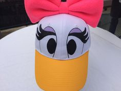 White baseball cap that has been embellished in the Daisy Duck Style. The glitter eyelashes are painted on. Perfect for dress up, a family vacation or