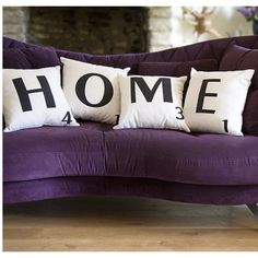 Scrabble cushions and purple couch with brick walls and wood floors<3