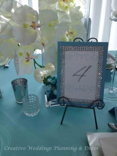 More bling in the table numbers (designed by Creative Weddings Stationary Designs). Centerpiece arrangements consisted of white phalaenopsis orchids in cube or rectangular glass containers that lined the feast table (designed by Creative Weddings Floral Designs).