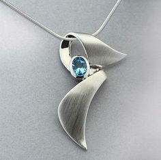 This brilliant blue topaz is bezel set and sits on a contemporary silver ribbon blowing in the caribbean wind. This is a unique, nicely made pendant that gives the awareness symbol a fresh twist. This #silverjewelry