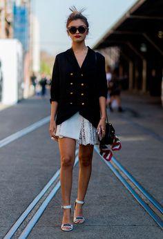 Street style look com vestido branco curto de renda com blazer oversized abotoado e sandália de salto branca.