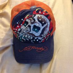 """Ed Hardy hat Orange mesh back. Blue denim front. Swarovski crystals (none are missing) design is skull as a motorcycle on fire. Orange stitching on rim of hat saying """"Ed Hardy"""". Hat WAS in perfect condition until about 12 hrs before I took these pics (snaps in back were chewed off). My puppy doesn't know we're moving but she knows something's happening & has been such a rebellious stuck up brat. It still works just has one snap left. If I can fix it I will change the price but price listed…"""