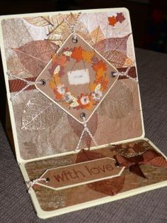Autumnal easel card.  Collaged patterned paper and angel hair, embossed cardstock, ribbon, cord and three-dimensional stickers.