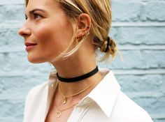 Pandora Sykes in a white button-down, black choker, and gold accessories