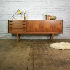 A stunning and very rare early teak sideboard c.1950s manufactured by E-Gomme (Later became G-Plan) –Superb original condition Featuring simplistic, angled solid teak handles, recessed door handles and four good sized drawers. A great feature of this sideboard is its sliding doors making it ideal for use as a media cabinet allowing full access to devises such as SKY/TIVO boxes, DVD playes and games consoles. The teak has a lovely vintage golden patina that only age can achieve. Dimension...