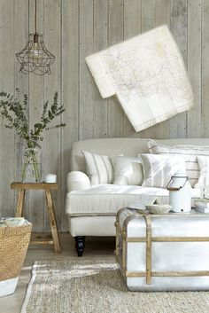 Think outside the box with walls clad in whitewashed planks and a homespun jute rug on the floor. A soft white linen sofa completes this natural country look. Photography: Mark Scott. Find more living room ideas at housebeautiful.co.uk