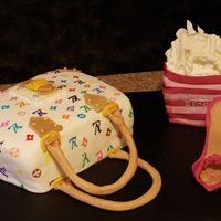 The purse cake is covered in fondant and the Louis V insignia was handpainted on. The purse bag's handles and accents were done in gumpaste. The VS shopping bag is cake and cereal rice treats covered in gumpaste with handpainted highlights and...