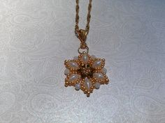 """:Starflower"""" pendant from Deborah Roberti (around the beading table) using white pearl diamonduos, toho gold seed beads and  3mm fire polish in metallic gold and milky opaque white. Loving this pattern and will make more pendants :)"""