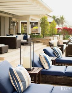 The patio, located just steps down from the loggia, is appointed with a row of comfortable Summer Classics wicker chaise lounges and accented with striped pillows made from a Ralph Lauren Home fabric.