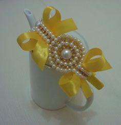 Tiara encapada em fita cetim amarela, com casquetes em meia pérola, pérolas e strass com laços em fita cetim muito charmosa.