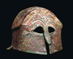 Pseudo-Corinthian helmet, 5th century B.C.  With false eye-holes and nose-guard, moulded eyebrows above, traces of incised decoration (later highlighted in white) include stylized hair locks over the brow, palmette flanked by snakes above, and a decorative border around the helmet perimeter, flange at rear, 17 cm high. Private collection, from Christie's auction