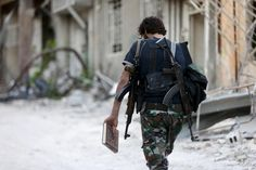 SYRIA. Jobar. July 2015. A Free Syrian Army fighter carries a copy of the Koran as he walks along a street in Jobar, a suburb of Damascus.Photograph: Bassam Khabieh/Reuters