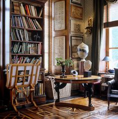 Axel Vervoordt ~ Architectural prints line the walls of the library which has a round Empire table in the corner