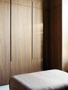 Natural timber wardrobe with minimal joinery and concealed handles makes the most of the timber grain