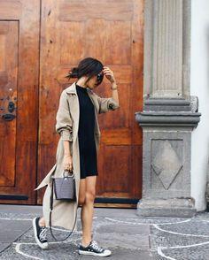 Chica usando un vestido negro corto, gabardina y tenis negros