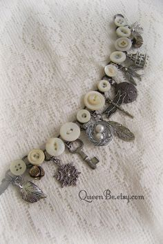12 unique nature themed charms adorn this bracelet assembled with vintage buttons. Made from old found objects, unique nature themed charms (including a hand wrapped birds nest with freshwater pearls) and several styles of vintage white buttons. Very comfortable to wear, and perfect for the vintage and antique lover. Every piece has been aged to coordinate with the wonderful old patina of the buttons. Some of the buttons still have the original thread in place! Zoom in to see the different…