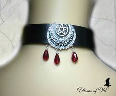 One inch wide black leather choker has antique sterling plated filigree crescent and silver tone pentacle. Three blood red teardrops hang below the crescent. Inside wiring is covered with felt for your comfort and choker closes with leather ties. Choose your preferred size.