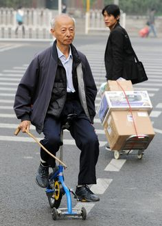 An elderly Chinese man rides his micro-bike in Beijing on October 22, 2011.