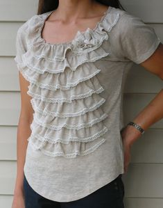 Getting tired of your old t-shirts? Turn them into a stylish ruffled top! You only need two of the same shirts, lace, and two small buttons.