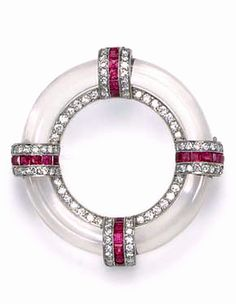 AN ART DECO ROCK CRYSTAL, RUBY AND DIAMOND BROOCH  Designed as a openwork rock crystal circle, the inner rim trummed with circular-cut diamonds, and enhanced at the cardinal points with a triple-row circular-cut diamond and calibré-cut ruby panel, mounted in platinum, circa 1930