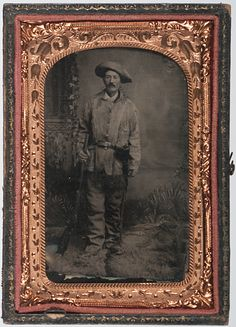 Tintype of Western character wearing fringed buckskin jacket and pants holding rifle with holster slung at his waist.