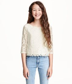 Gently flared lace blouse with 3/4-length sleeves, an opening with a button at the back of the neck and a jersey lining.