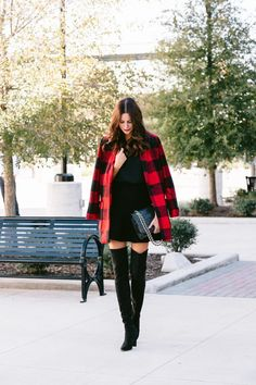 Amanda Miller wearing a pair of black suede over the knee boots paired with a camisole, black skirt and a plaid jacket.