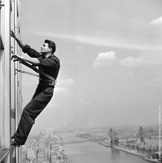 A window cleaner at work at the United Nations Secretariat building in mid-town Manhattan, overlooking the East River, New York. The building has 6,000 panes of glass in its two transparent facades, and the 7 cleaners take a month to complete the job. (Photo by Douglas Grundy/Three Lions/Getty Images). Circa 1955