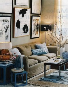 layering of rugs, gallery wall of artwork, blue and neutral palette with accents of black and gold.