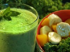 Healthy green smoothie- ice, water, grapes, peach, banana and spinach