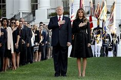 U.S. President Donald Trump and first lady Melania Trump, flanked by White House staff, place their hands over their hearts on the South Lawn of the White House during the playing of 'Taps' at a ceremony marking the September 11 attacks September 11, 2017 in Washington, DC. Today marks the 16th anniversary of the attacks that killed almost 3,000 people and wounded another 6,000.