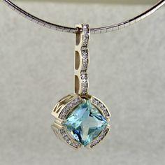14 karat white Gold with Ideal cut Diamonds surrounding this magnificent Princess cut mint Beryl.
