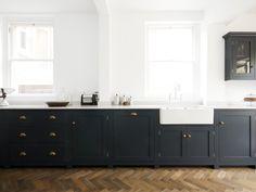 piso de madeira e armários pretos em cozinha