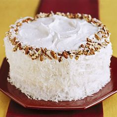 COCONUT PECAN LAYER CAKE -  Frosted with swirls of fluffy frosting and trimmed with coconut and pecans, this festive cake recipe is just the ticket when you need a special occasion dessert. Underneath the snowy white frosting are two layers of yellow cake flecked with more coconut and pecans.
