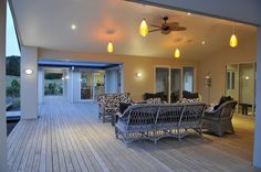 This home features expansive decking along the length of the house, in between the home and the pool.