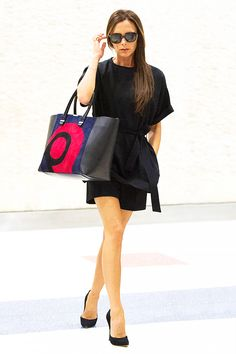 Victoria Beckham in a black ensemble with a vibrant bag