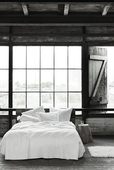 Exposed beams, wood ceiling, huge windows, white bedding...what a dream room!