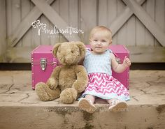 one year baby girl birthday photos in pink suitcase with teddy bear and pink chevron dress