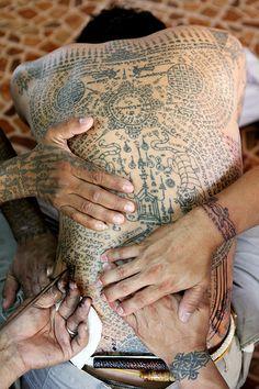 A Thai man getting a Sak Yant tattoo on his back at Wat Bang Phra temple, Nakom Pathom province, Thailand  √
